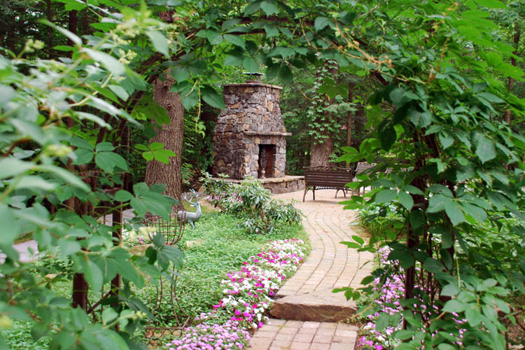 Stone walkway bordered by flowers leading to outside fireplace and bench
