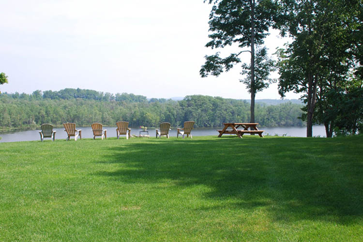 Lawn with Adirondack chairs and picnic table in background, lake in background