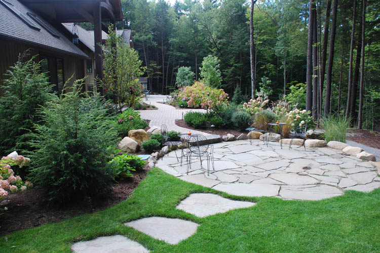 Stone walkways to patio containing patio furniture