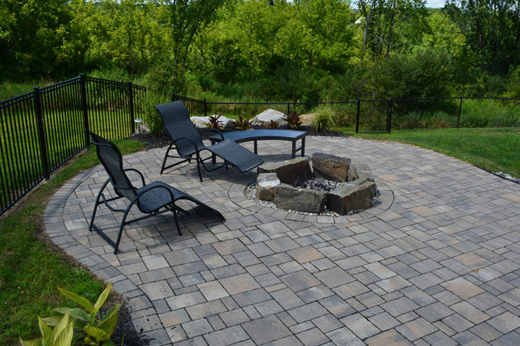 Stone patio with chairs and firepit