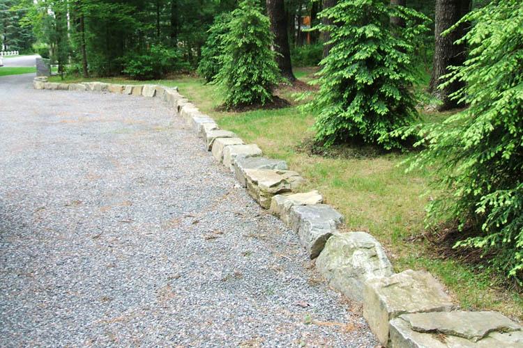 Stone wall boarding stone driveway