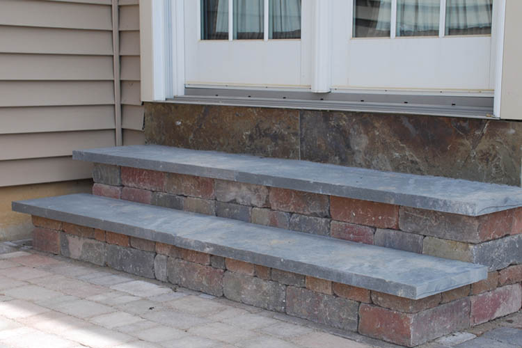 Stone steps with flat top, leading to double doors