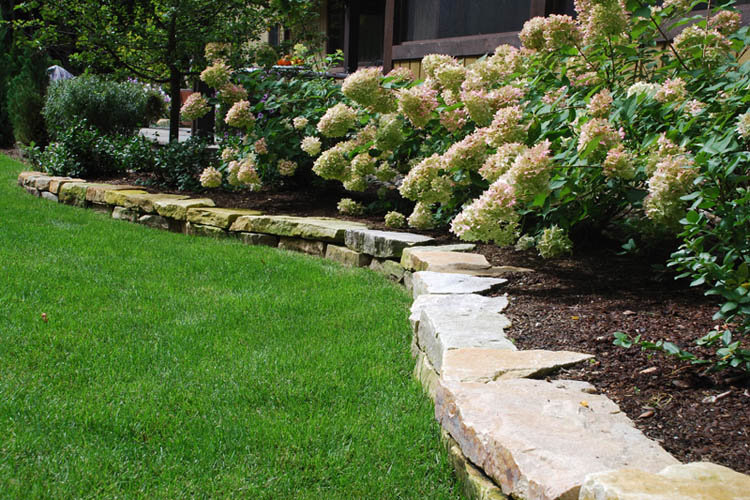 Stone wall bordering grass and flower beds