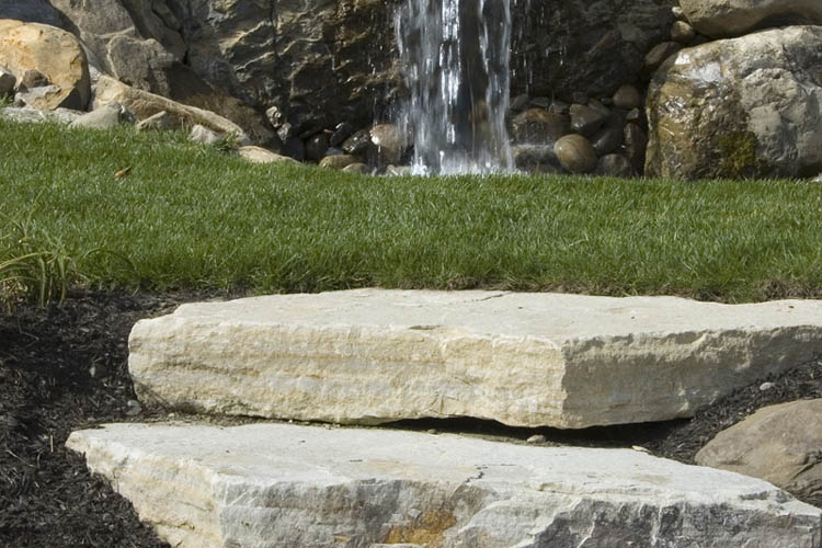 Large stone steps in front of water feature