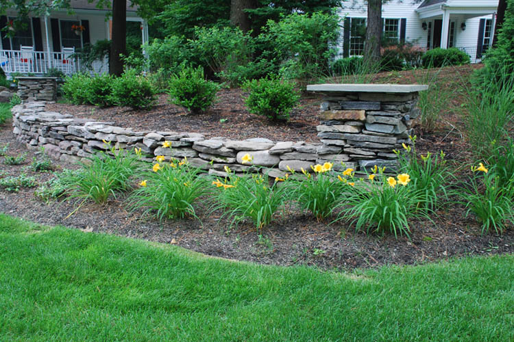 Stone wall with flower bed in foreground