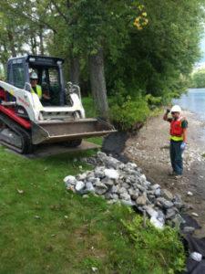 Contruction equipment moving rocks on lake shoreline