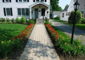 Sidewalk bordered by flower beds leading to house entrance